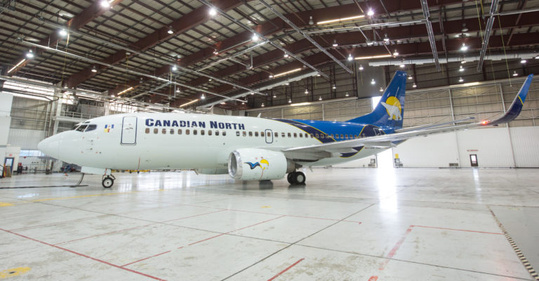 A Canadian North Boeing 737-300 aircraft rests in the main hangar bay at Edmonton International Airport.