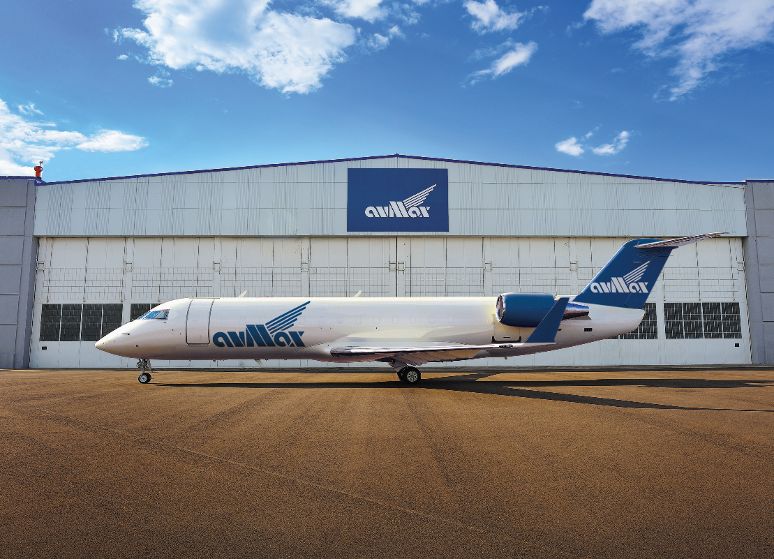 A Bombardier CRJ aircraft rests outside an Avmax hangar.