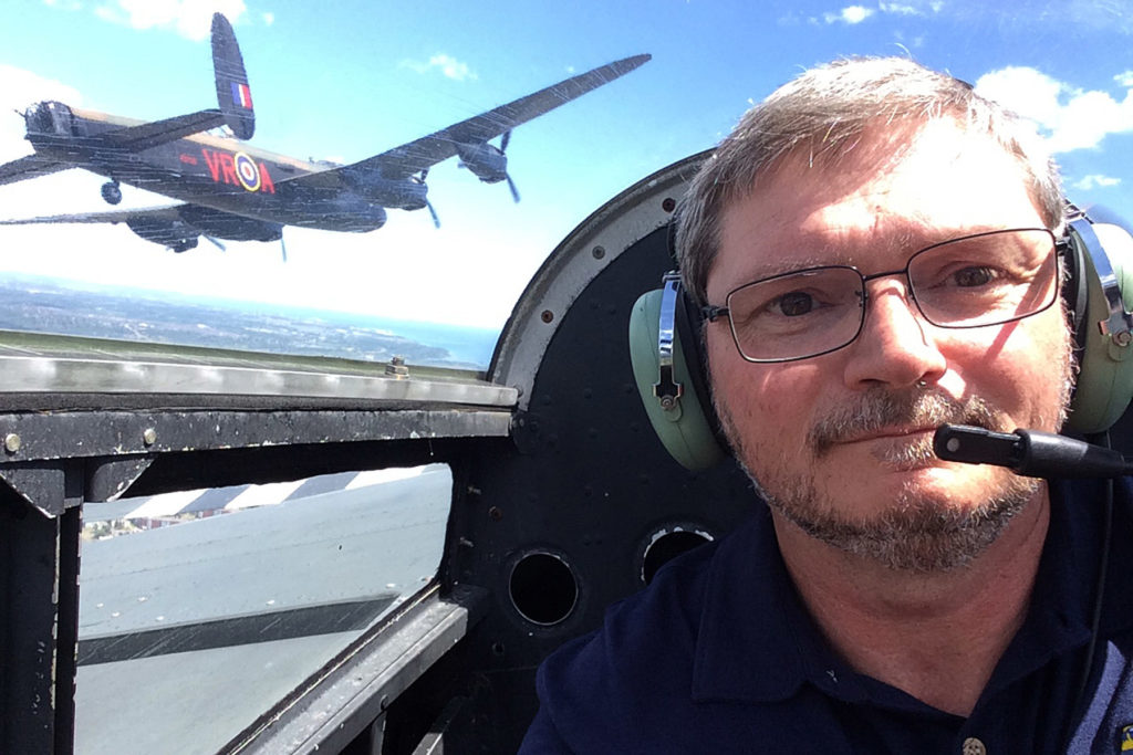 Dumigan in cockpit of an aircraft, with Lancaster in the background
