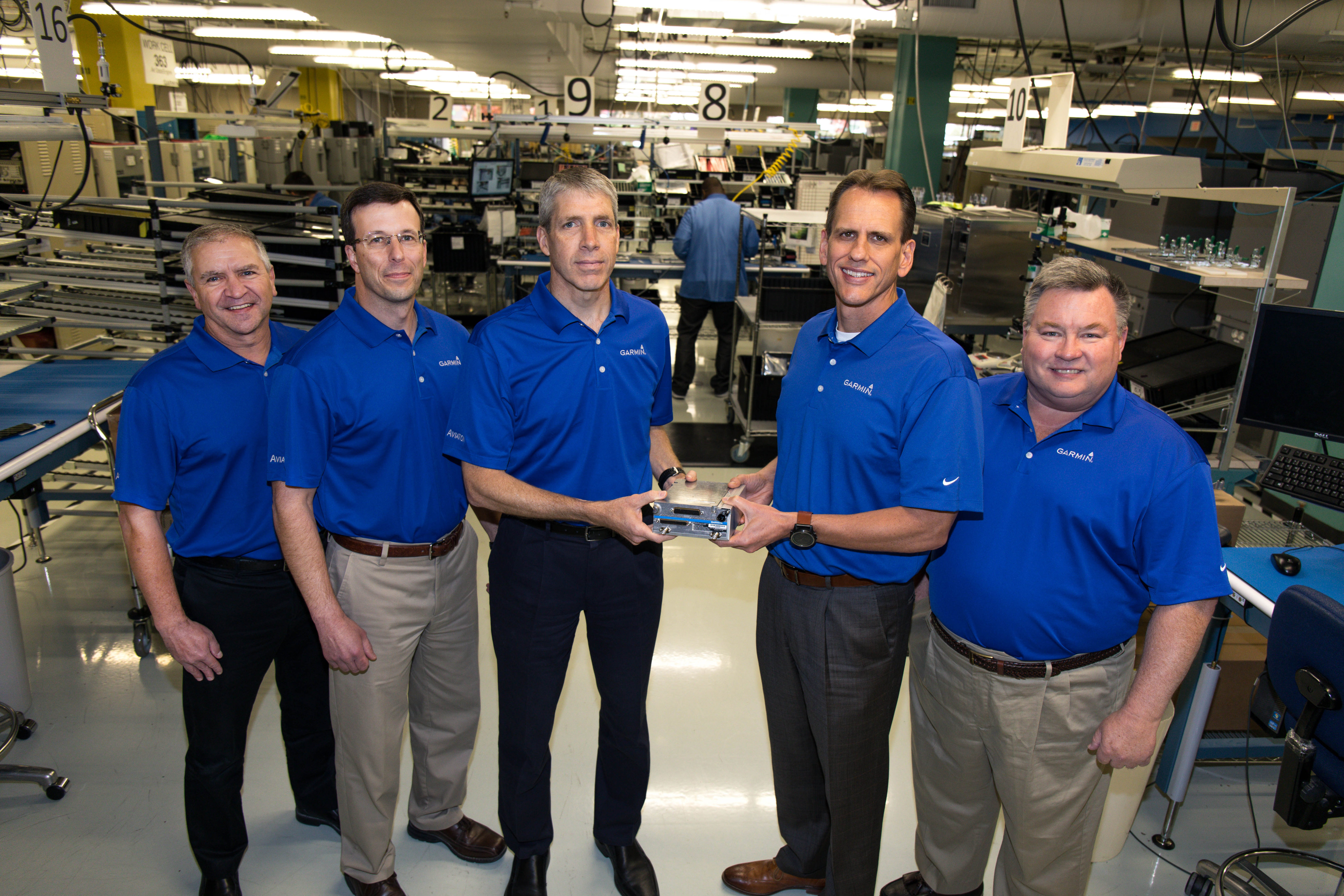 Five men stand in a horizontal row, with the middle two holding the GTX 3000 transponder.
