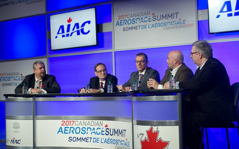 Five men sit at a table, in front of an audience, during the panel discussion