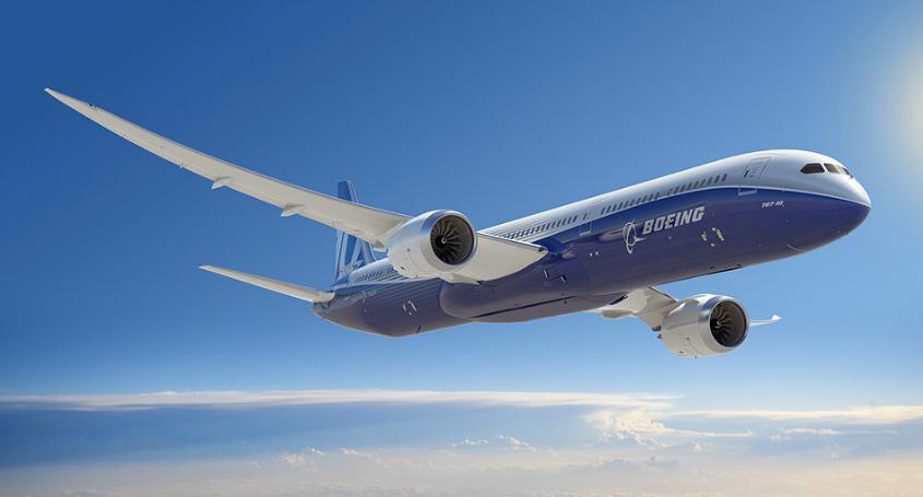 Boeing 787-10 Dreamliner soaring above clouds.