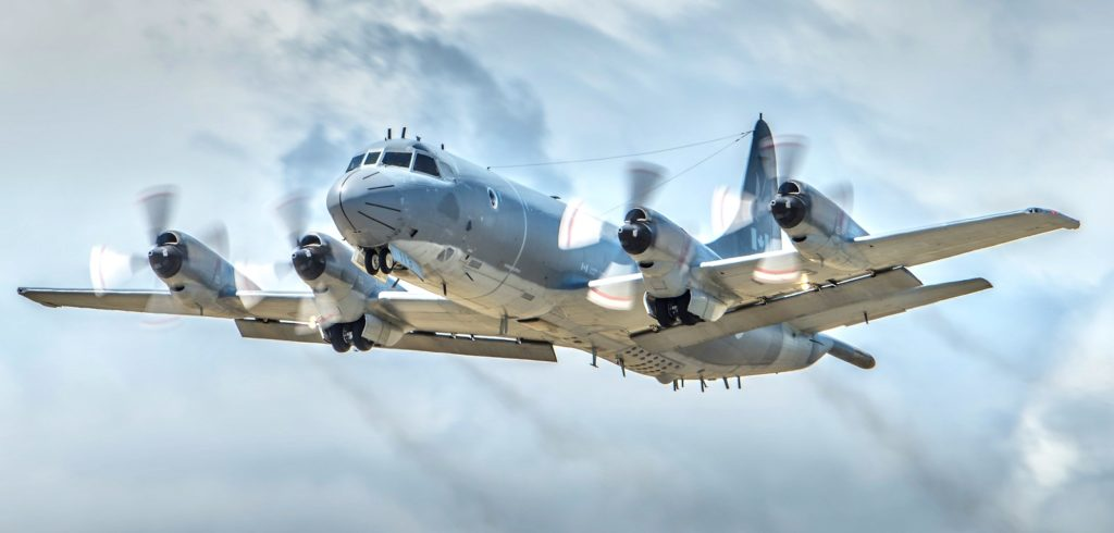 CP-140 Aurora flying through party-cloudy skies