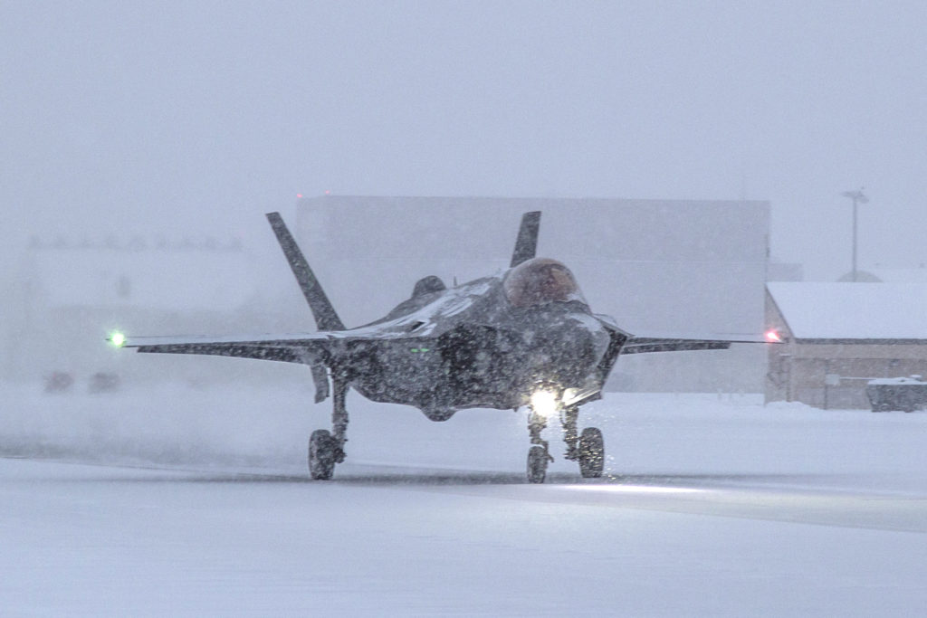 "Maj Jonthan ""Spades"" Gilbert, taxis as snow falls on his F-35A fighter jet at Eielson Air Force Base in Alaska."