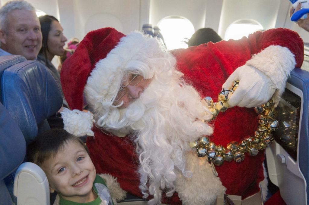 Santa poses with boy.