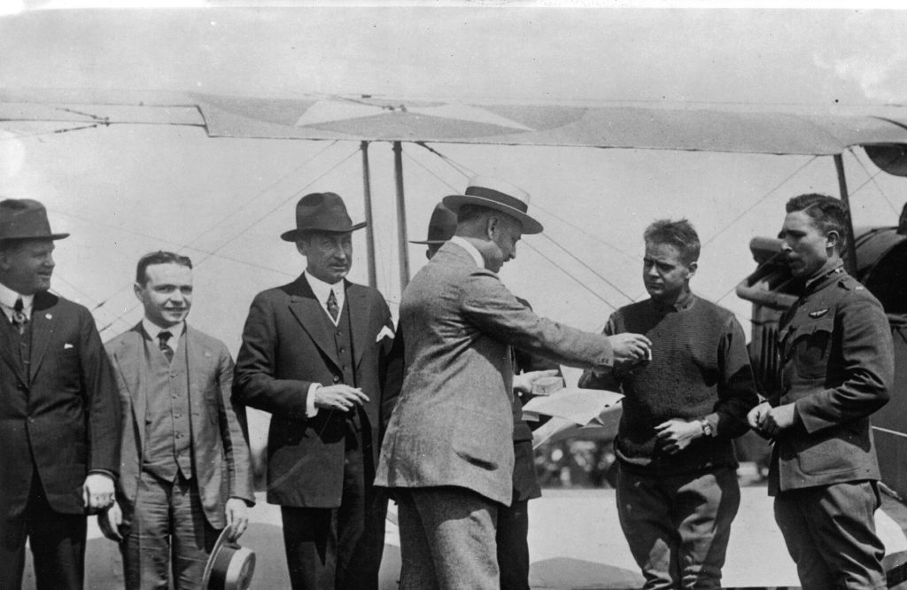 Black and white photo of man handing out watches to pilots