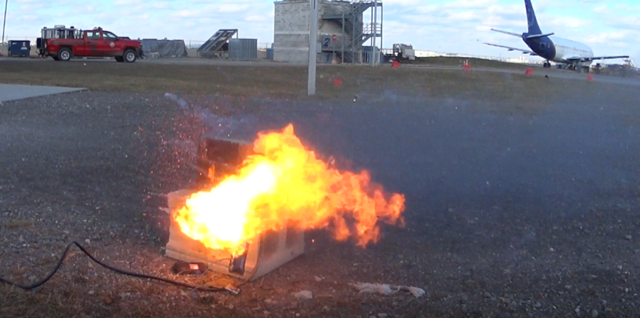 A reserve capacity (RC) battery bursts into flames atop a cinder block.