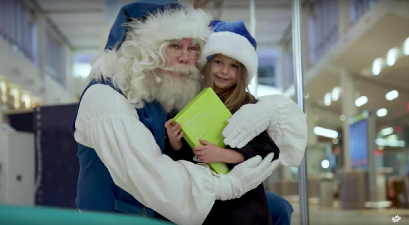 WestJet Blue Santa poses with girl in blue Santa hat.