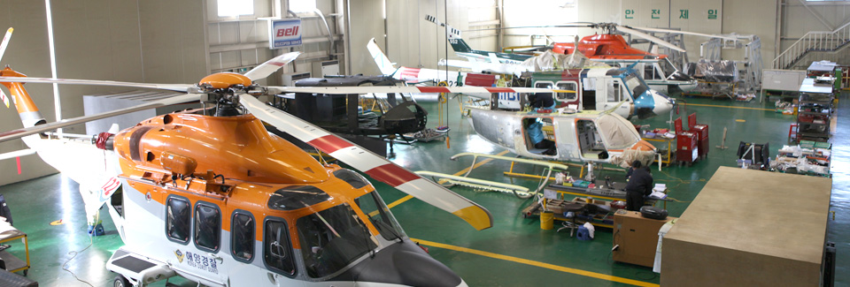 Several helicopters rest in a hangar