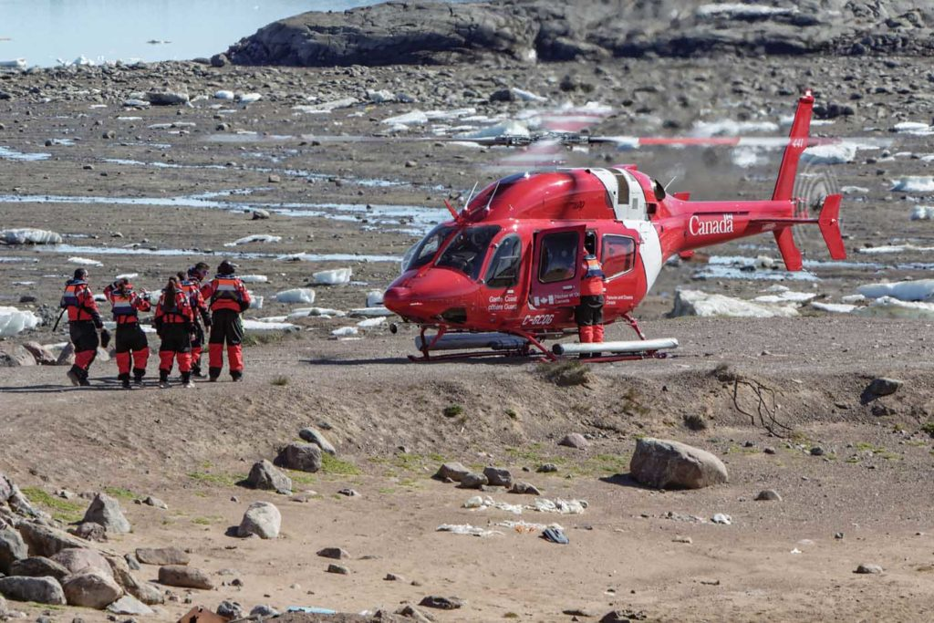 Coast Guard helicopter and rescue workers rest on ground
