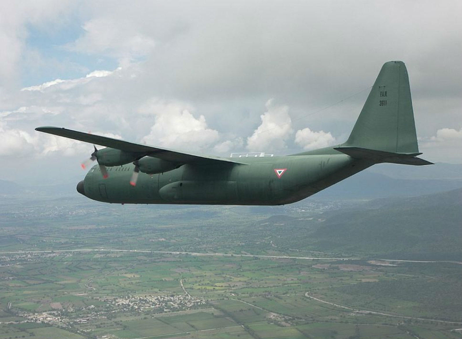 A Fuerza Aérea Mexicana L-100 (C-130) Hercules aircraft, in flight.