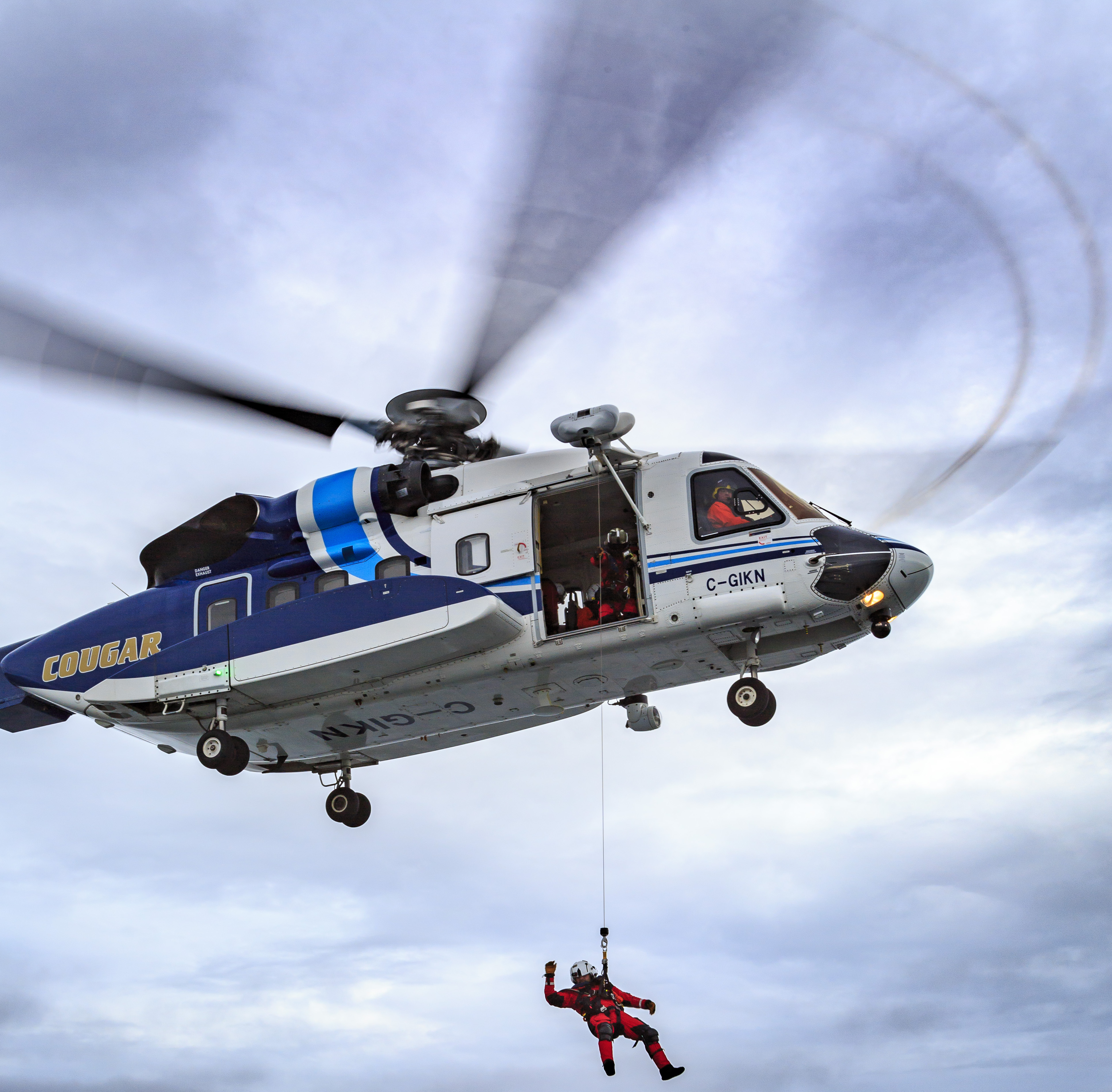 Cougar Sikorsky S-92 helicopter with rescue working hanging below it on longline