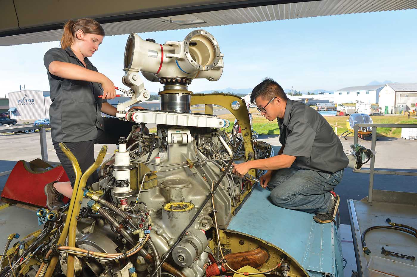 Aircraft maintenance engineer Tessa Ferneyhough, left, works on a Sikorsky S-76
