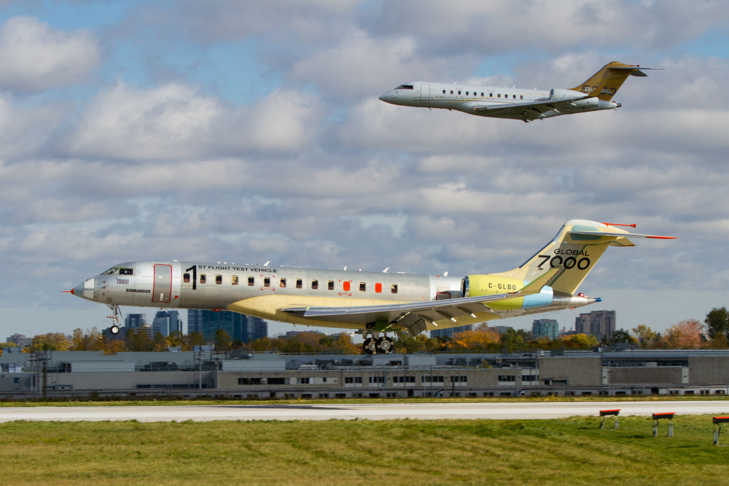 Two business jets, one flying and one on the ground.