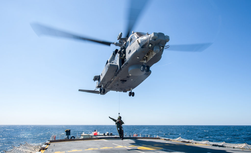A member of the flight crew is lowered from a CH-148 Cyclone helicopter on to the flight deck of Her Majesty's Canadian Ship (HMCS) Montreal on April 20, 2016,