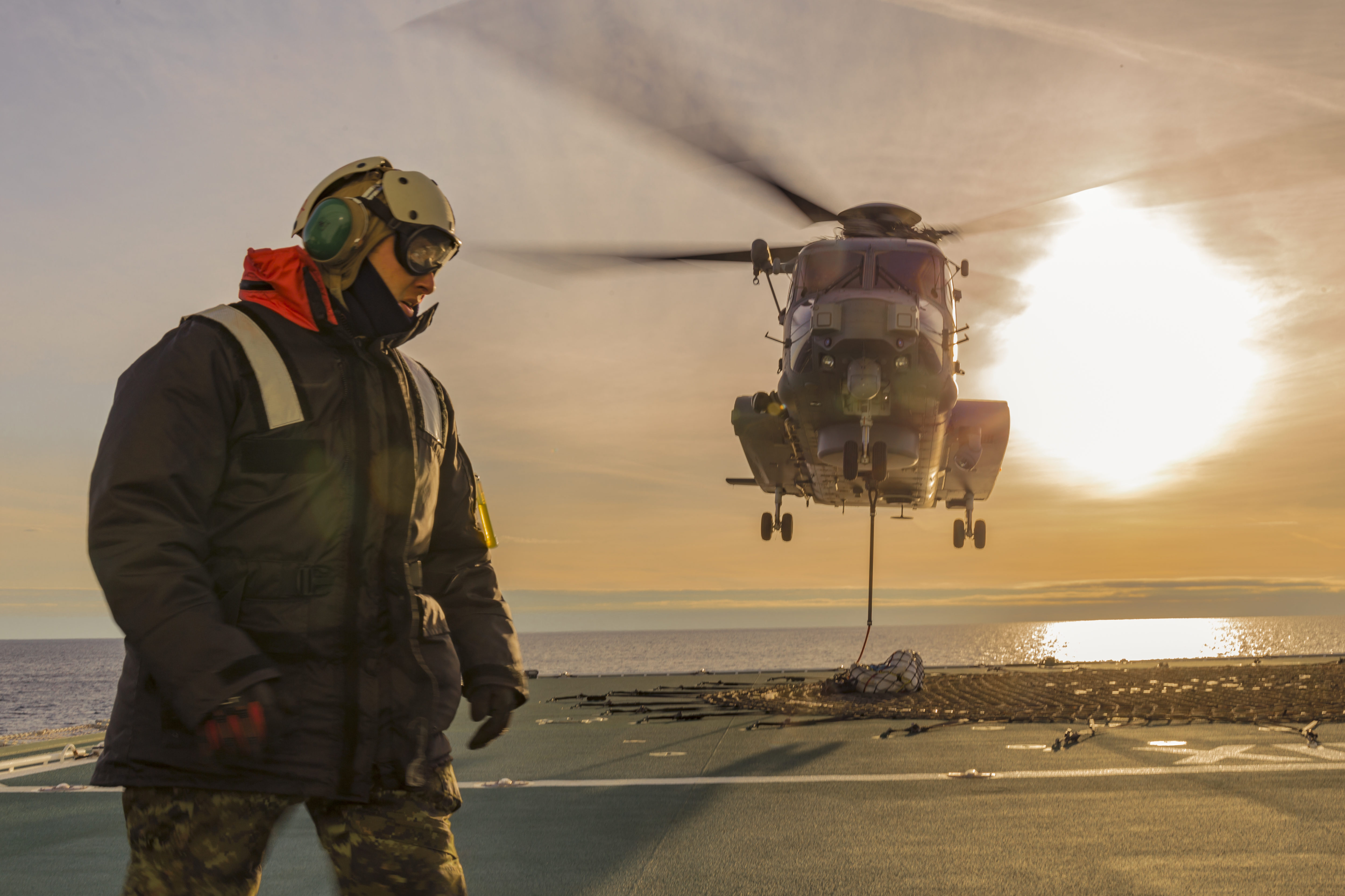 A Royal Canadian Air Force CH-148 Cyclone helicopter hovers over the desk of Asterix, a Resolve-Class Naval support ship.