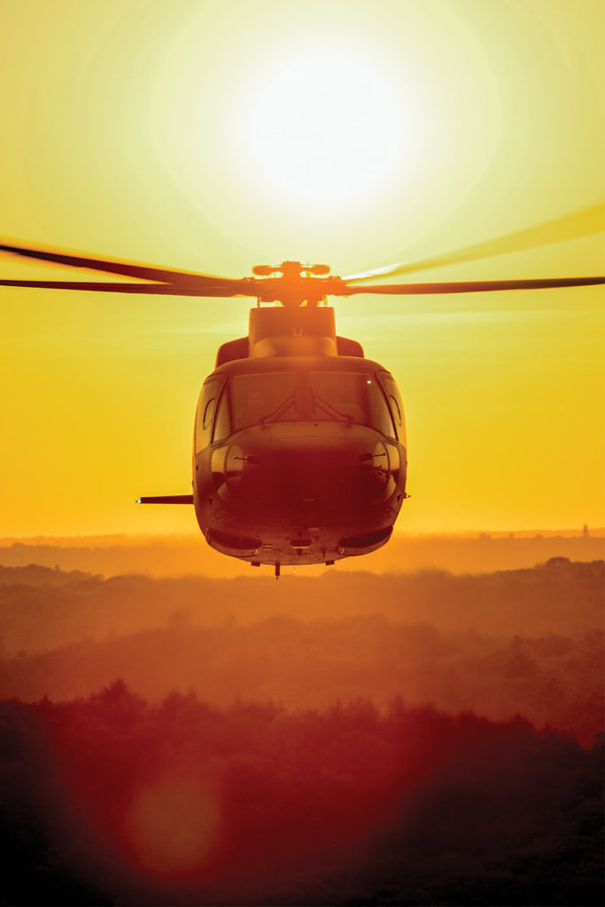 Helicopter flies with sunset in background
