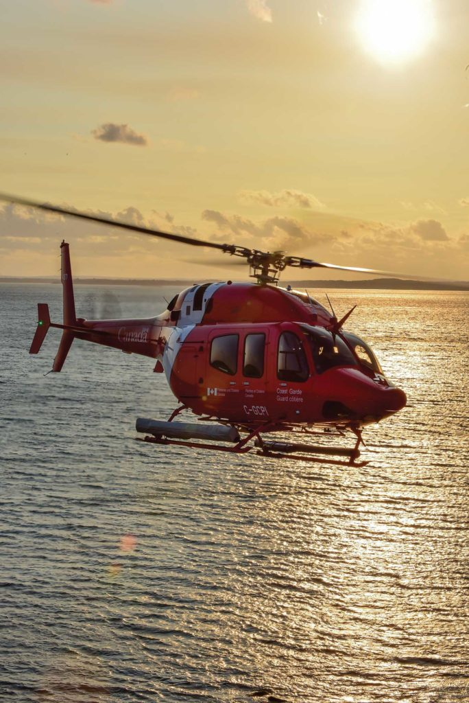 Coast Guard helicopter flies at sunset