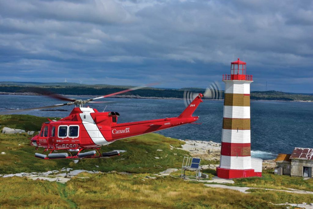 Coast Guard helicopter flies with lighthouse in the background