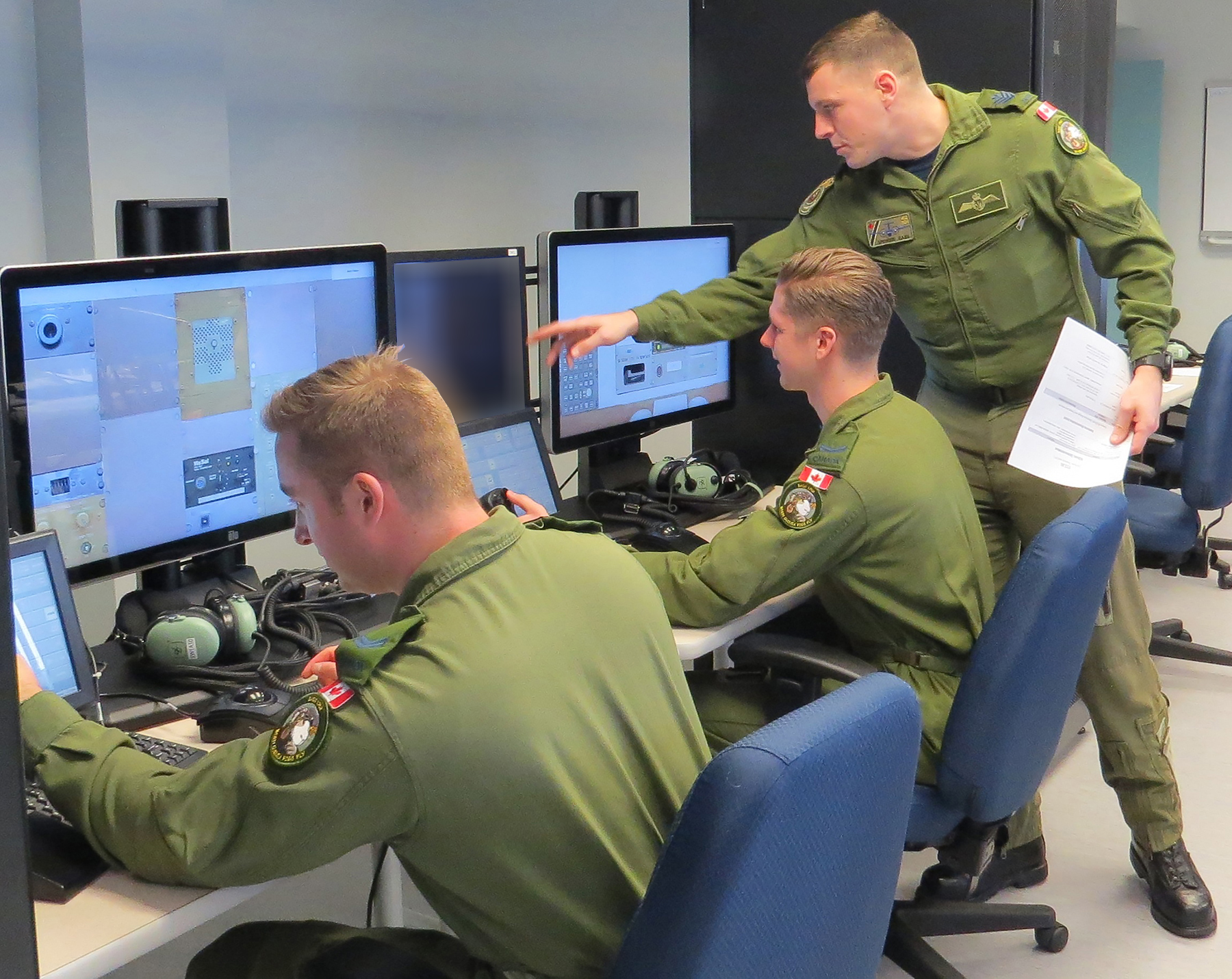 Sgt Spencer Cass instructs AES Op students Cpl Matthew Denis (left) and Cpl Connor Slaunwhite on the newly installed procedural crew trainer system at 402 Squadron, located at 17 Wing Winnipeg, Man.