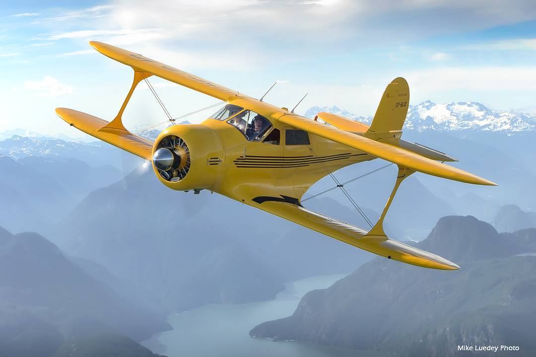 A yellow Beechcraft Staggerwing flying through the coastal B.C. Rockies. Photo submitted by Mike Luedey