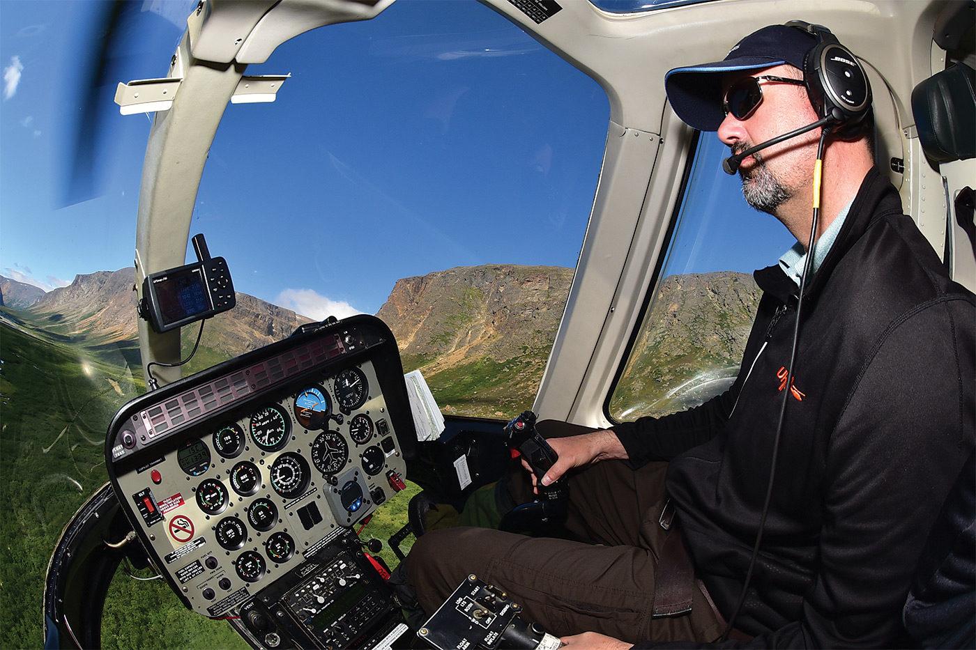 Helicopter pilot in cockpit, flying