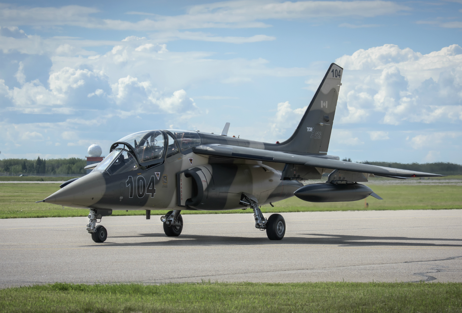 A Top Aces Alpha Jet rests on the ground.