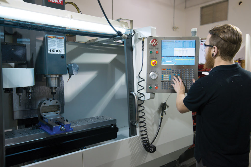 Machinist Eric Desmet operates the computer numerical control (CNC) machine in support of rotor blade repair tooling development.
