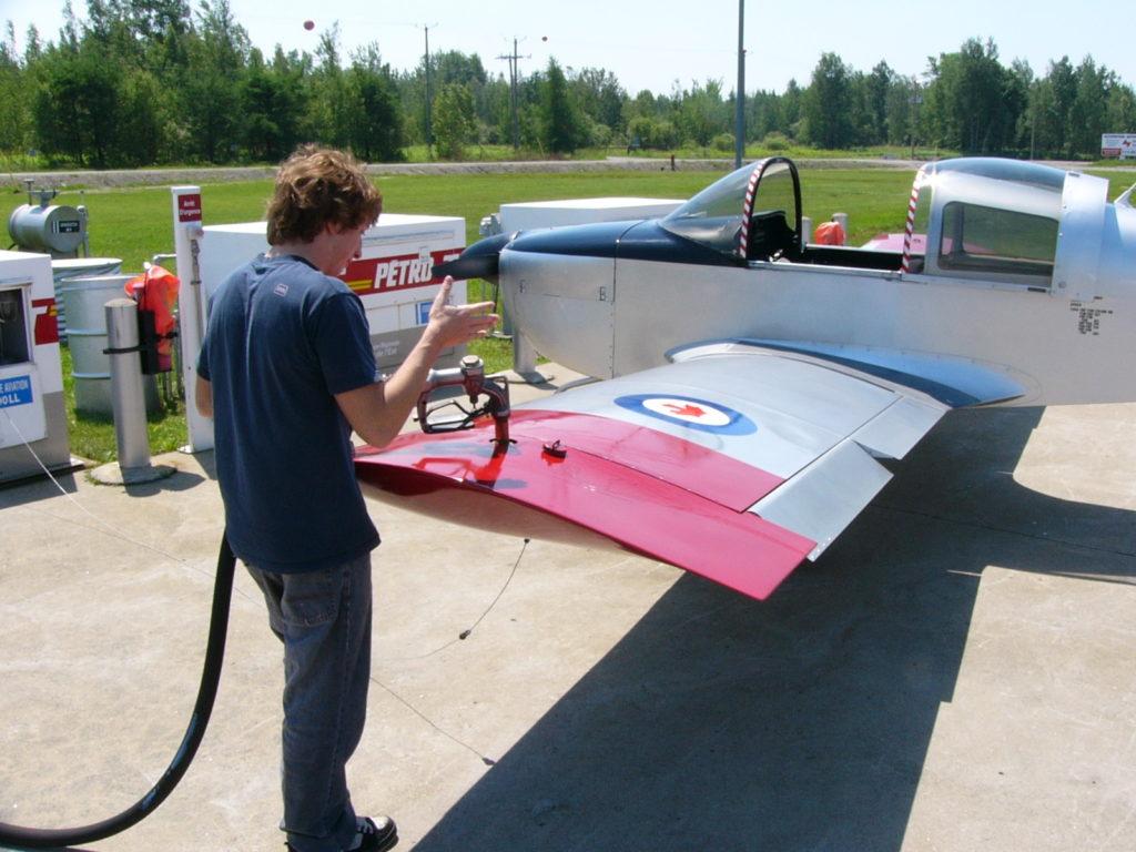 An attendant fills an aircraft with aviation gasoline.