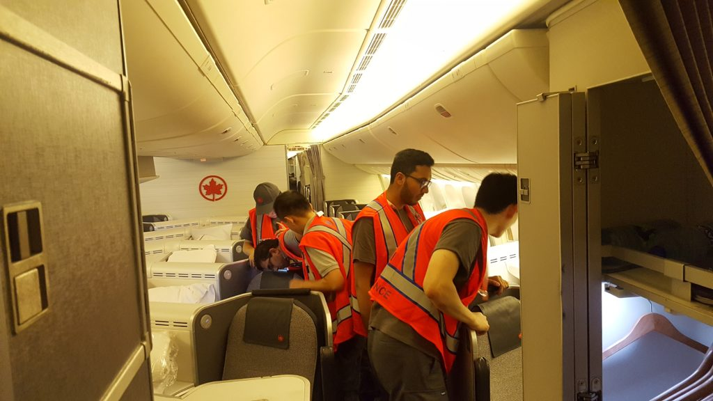 Students from Air Canada's work integrated learning program for aircraft maintenance engineers inspect an aircraft cabin while on a work placement.