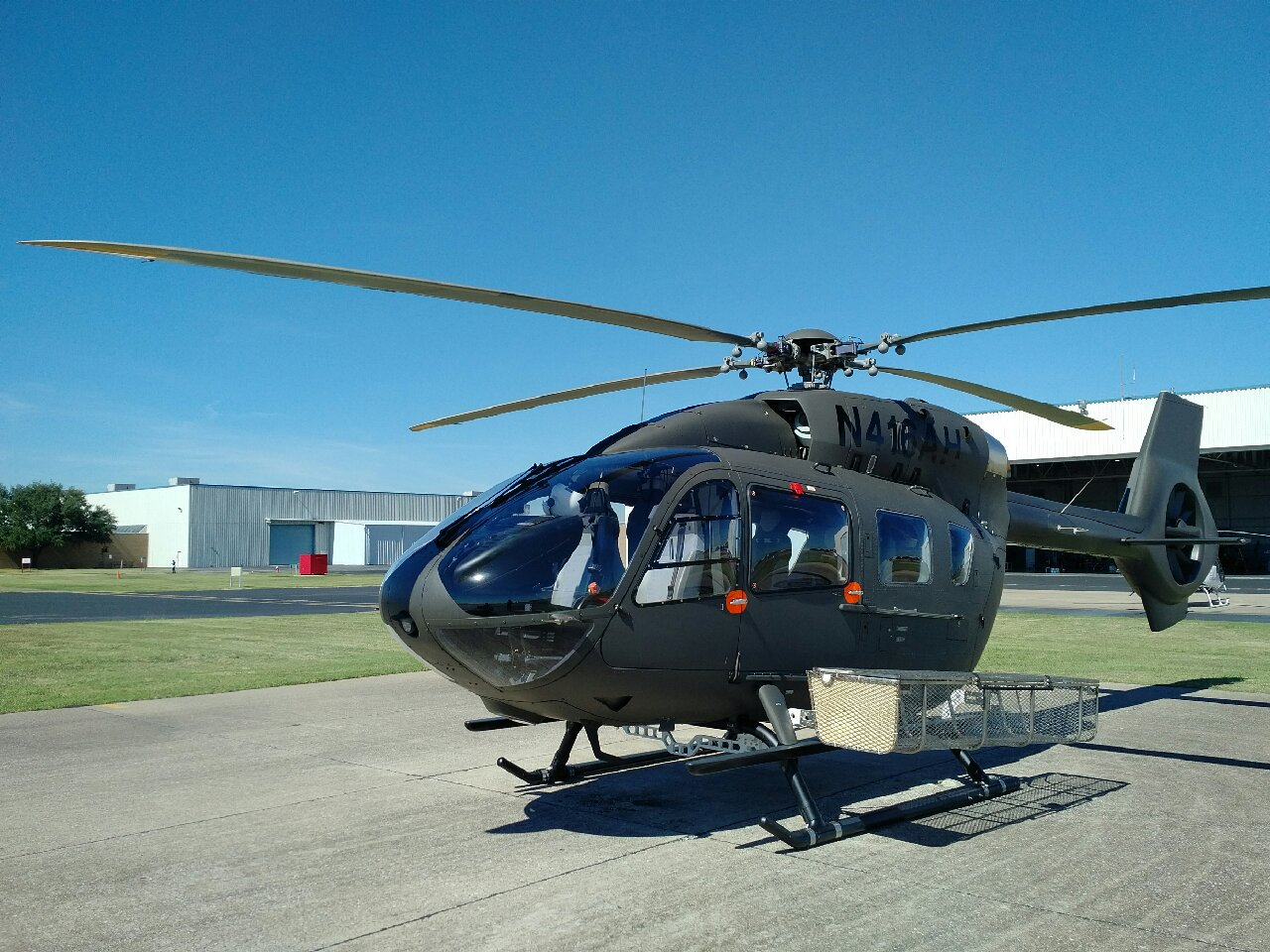 Helicopter rests on ground with basket attached
