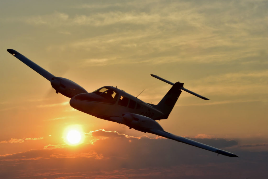 A Piper PA-44-180 Seminole flies over the Waterloo region of Ontario at sunset.
