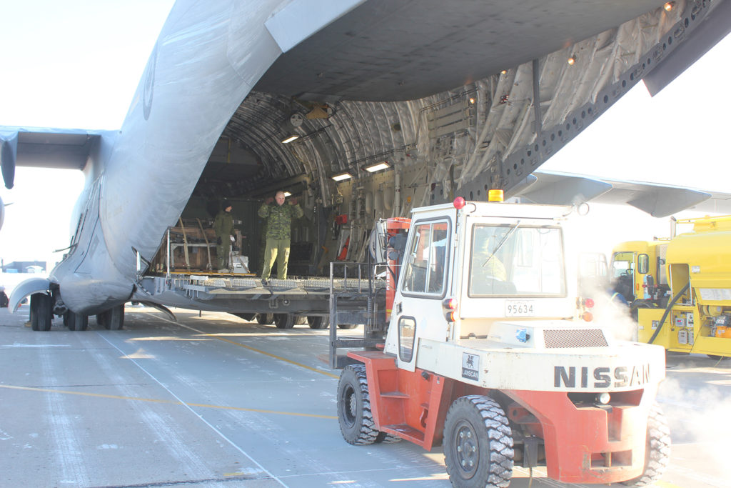 A traffic tech manoeuvres his front-end loader into position to receive 409 Tactical Fighter Squadron gear from a CC-177 Globemaster.