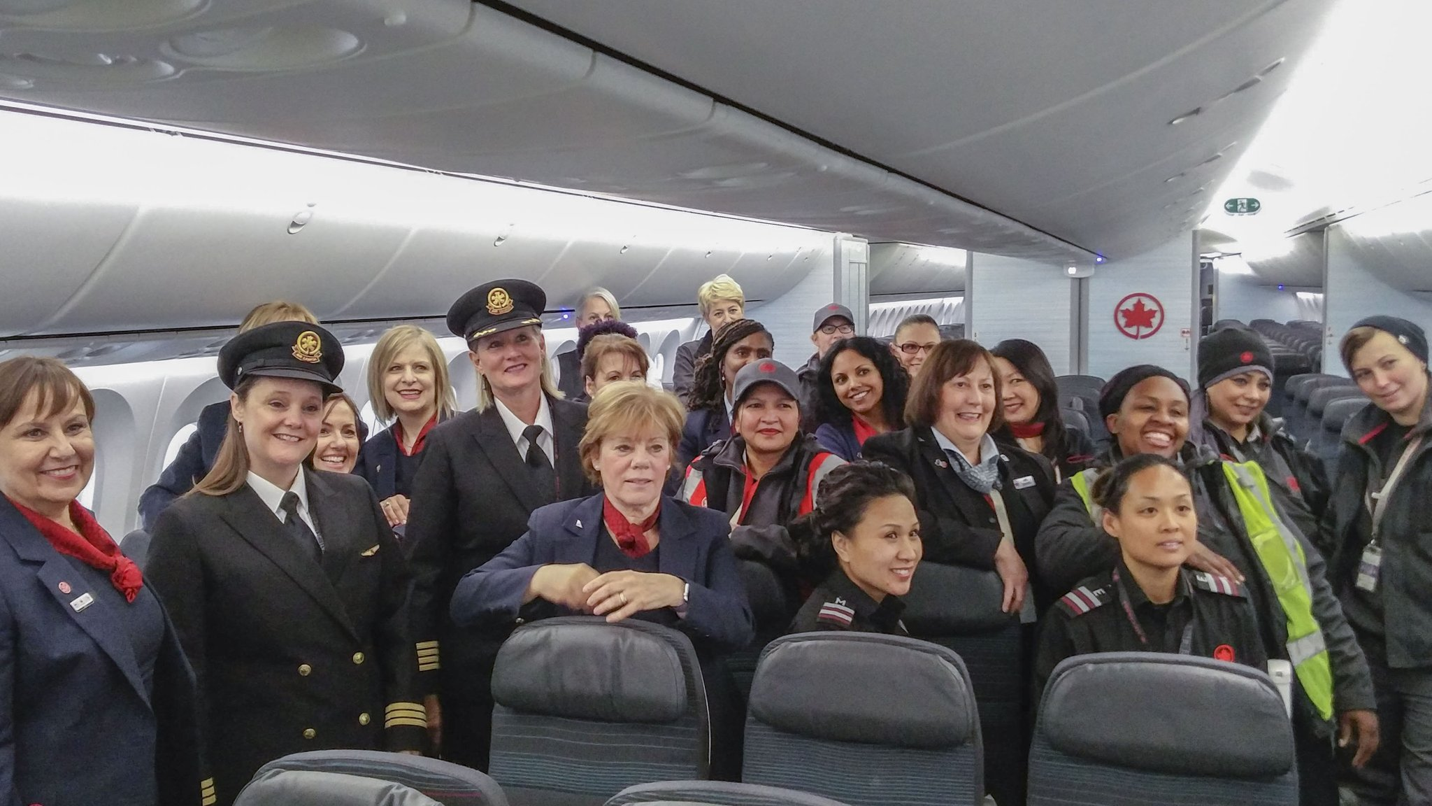 Women pose for photo inside plane
