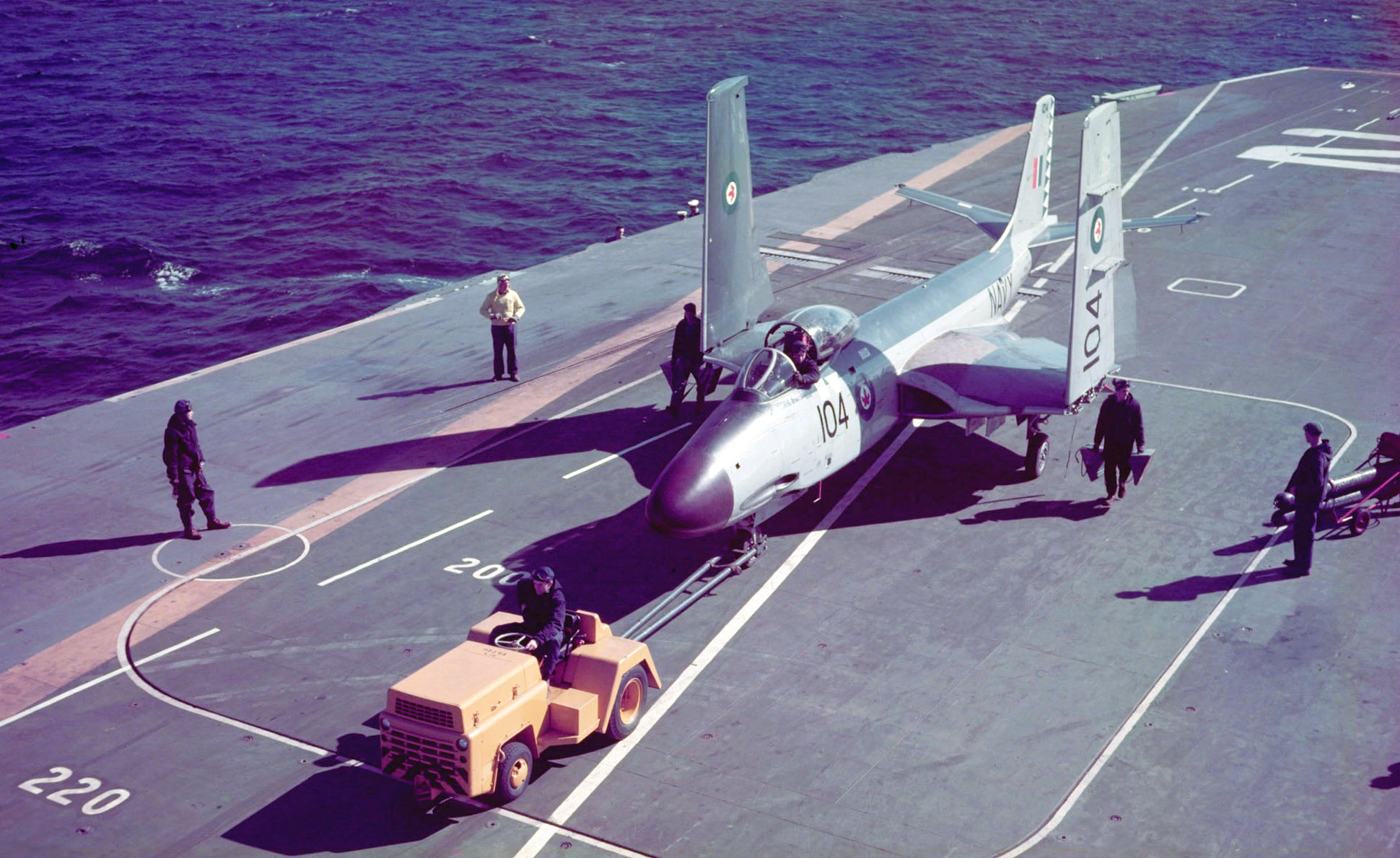 Mule pulling Banshee aircraft, wings folded, along the flight deck.
