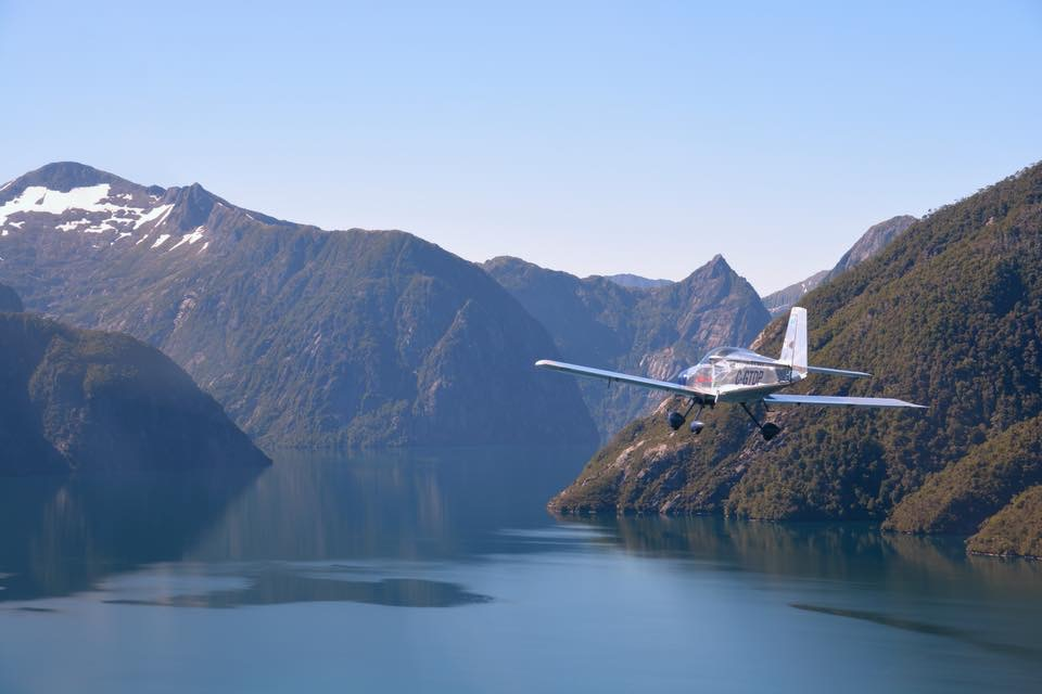 Plane flying over body of water, with mountains in the background.
