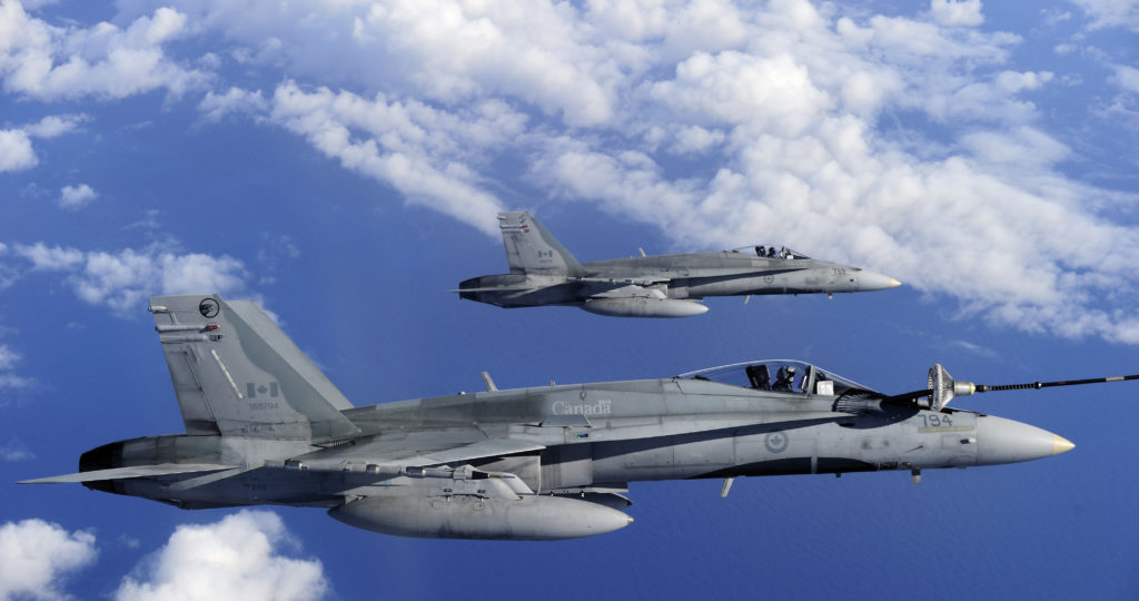 Two Royal Canadian Air Force (RCAF) CF-188 hornets from 425 Tactical Fighter Squadron in Bagotville, Que., get refueled by a RCAF CC-150 Polaris air-to-air refuelling aircraft from 8 Wing Trenton, Ontario, over the Pacific Ocean near Joint Base Pearl Harbor-Hickam, in Honolulu, Hawaii.