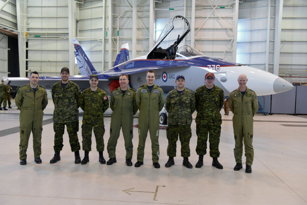 The 2018 CF-18 Demonstration Team stands with the demonstration Hornet.