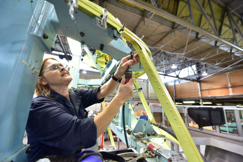 A woman works on an aircraft structure