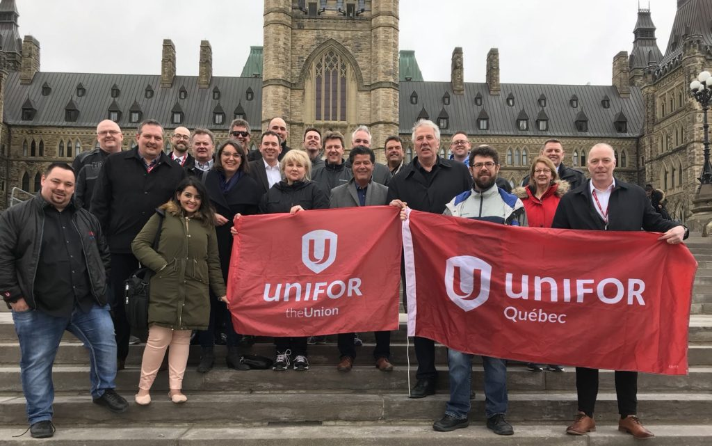 Several people stand on steps outside parliament buildings, holding Unifor flags.