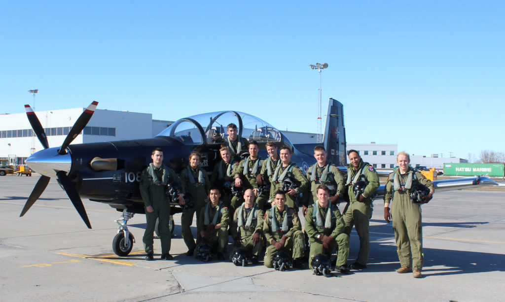 The 14 recent graduates of the NATO Flying Training in Canada Program stand with one of the CT-156 Harvard III aircraft they trained on at 2 Canadian Forces Flying Training School, 15 Wing Moose Jaw, Sask. DND Photo