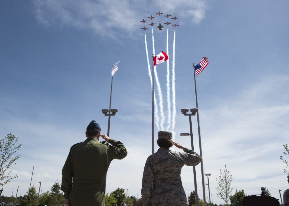 U.S. Air Force General Lori Robinson, Commander of the North American Aerospace Defense Command and U.S. Northern Command and Canadian Lt. Gen. Pierre St-Amand, the NORAD Deputy Commander salute during the playing of the Last Post and missing-man formation flyover by the Royal Canadian Air Force's Snowbirds aerial demonstration team on Peterson Air Force Base, Colorado, May 11.