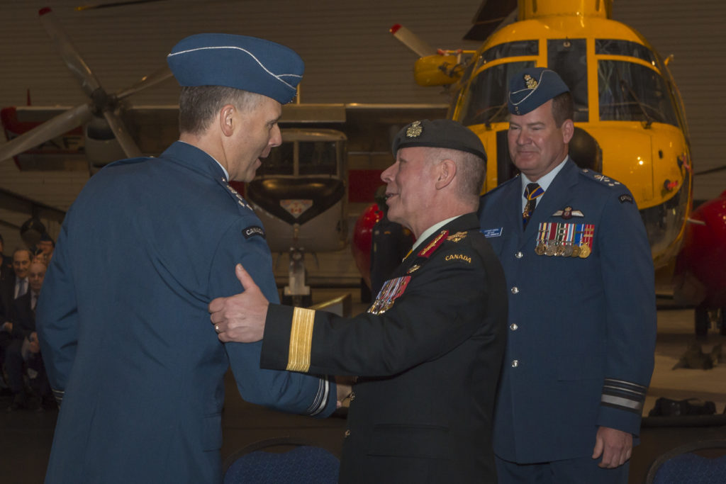 Incoming RCAF commander LGen Al Meinzinger, left, shakes the hand of Gen Jonathan Vance, chief of the defence staff, as outgoing commander, LGen Mike Hood, right, looks on.