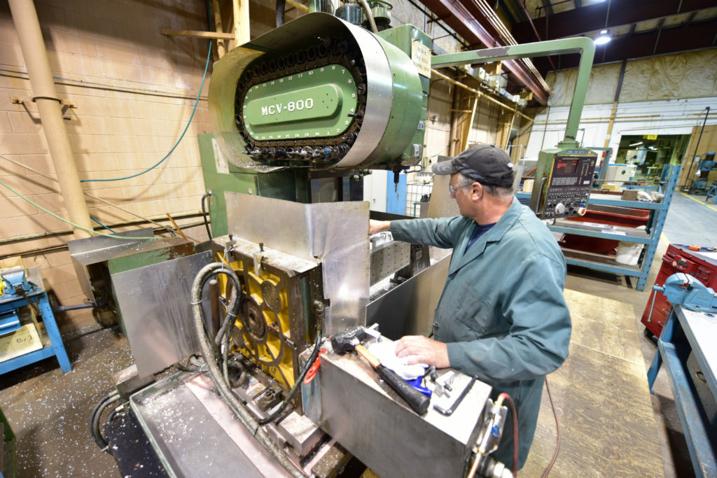 Man works on machine inside aircraft manufacturing facility
