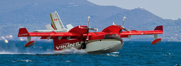 A Viking CL-415EAF aircraft moves along a body of water.