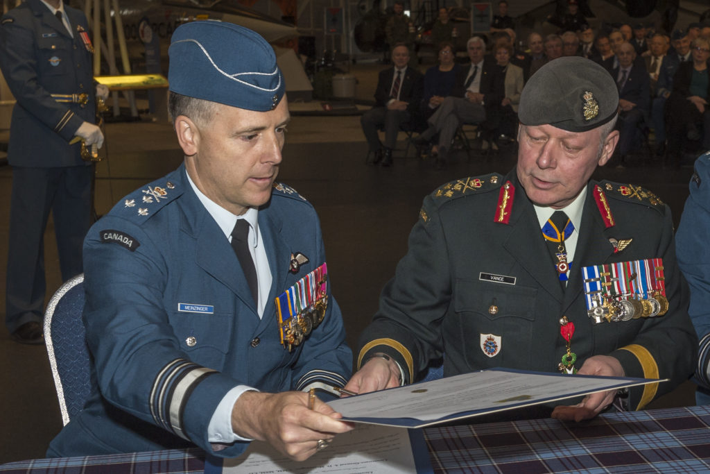 LGen Al Meinzinger, incoming RCAF commander, and Gen Jonathan Vance, chief of the defence staff, trade change of command documents to ensure all participants sign all copies of the documents.