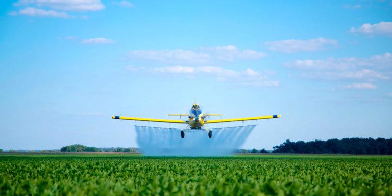 Air Tractor aircraft flies over field, spraying crop