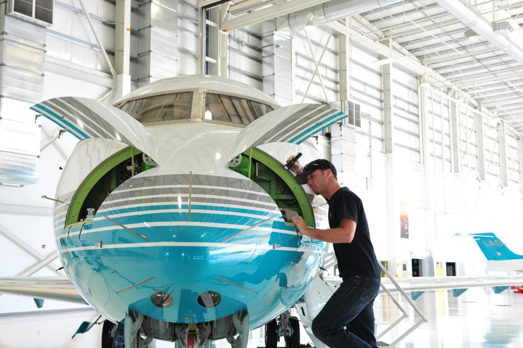 Man inspects jet inside hangar.