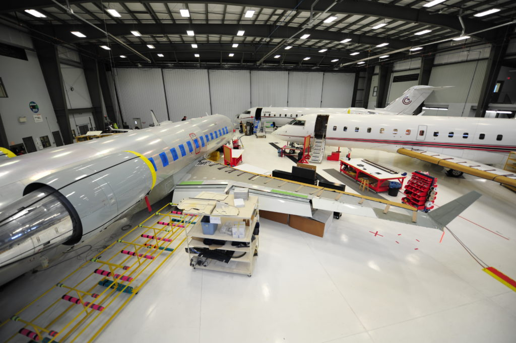Three aircraft rest in Flying Colours hangar