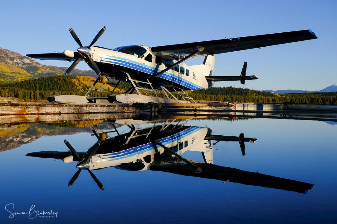 Evening light and still water combine to reflect this Alkan Air Ltd. Cessna 208 Supervan 900 on Schwatka Lake, Yukon. Photo submitted by Simon Blakesley (Instagram user @simon_blakesley) using #skiesmag